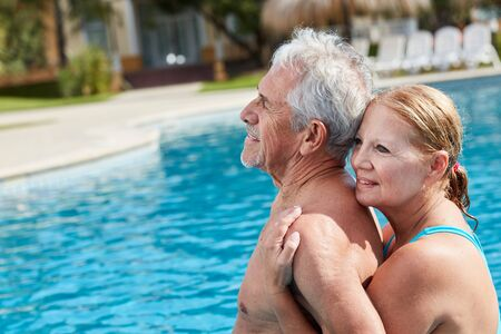 Happy senior couple in love relaxing by the pool at the Wellness Hotel Standard-Bild - 131352612