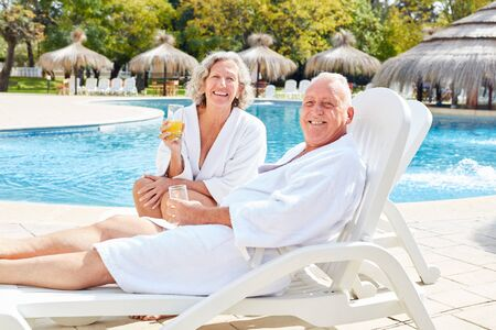 Happy seniors couple relaxing at the swimming pool of luxury spa hotel Standard-Bild - 131352614