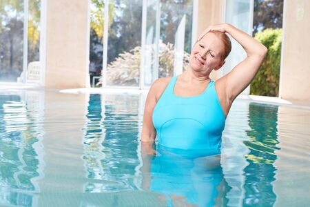 Senior woman makes healthy stretching for the neck during water aerobics Standard-Bild - 131352621