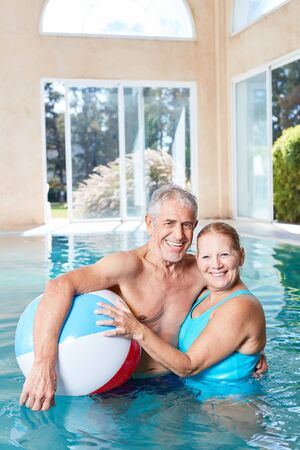 Happy seniors couple in pool of spa wellness hotel with beach ball Standard-Bild - 131352622