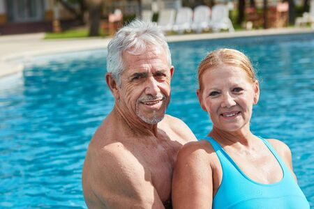 Happy seniors couple together at the swimming pool on wellness vacation Standard-Bild - 131352623