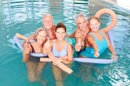 Vital seniors in the swimming pool with thumbs up in aqua fitness course Фото со стока