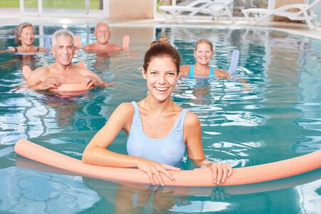 Woman as a physiotherapist makes aqua fitness as a rehab with seniors in the pool