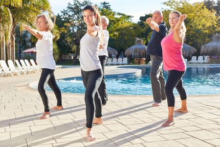 Senior group doing yoga fitness workout by the pool at Wellness Hotel