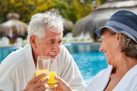 Happy seniors couple toasting with orange juice at the swimming pool on vacation Standard-Bild - 131352639