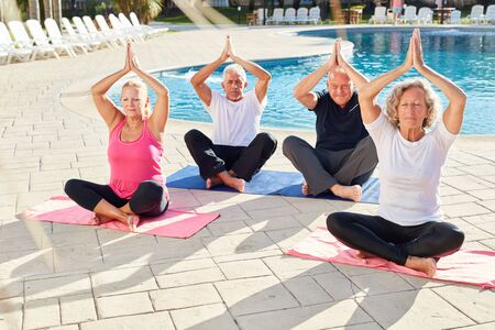 Group of seniors in the yoga class meditates together at the pool in the Wellness Hotel