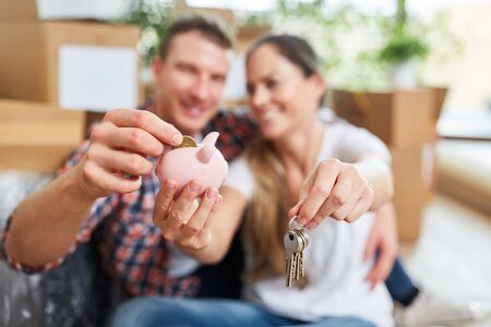 Happy couple in new home with piggy bank as symbol for finance