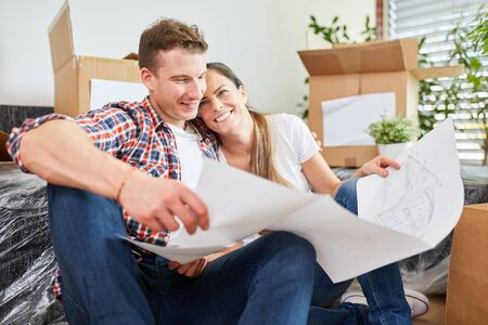 Couple in love planning home construction with construction drawing before move Stok Fotoğraf