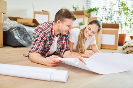 Happy young couple planning house building or house purchase with blueprint