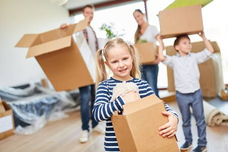 Girl helps the parents carry the moving boxes to the new home