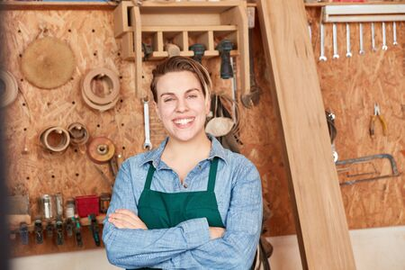 Happy young woman as carpenter apprentice with crossed arms in workshop
