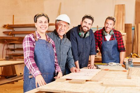 Group craftsman with master and colleagues together in joinery workshop