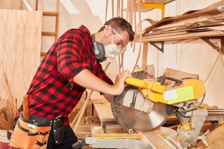 Schreiner oder Schreiner mit Atemschutzmaske an der Kappsäge in der Werkstatt