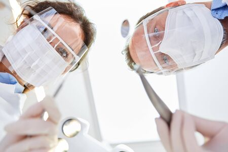 Dentists as a medical team with surgical mask and visor before surgery in the dental clinic