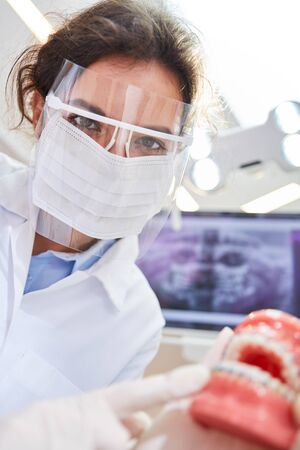 Woman as a dentist or oral surgeon with surgical mask and visor points to a denture model Standard-Bild