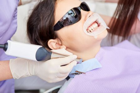 Patient at the professional cosmetic bleaching at the dentist in the dental office