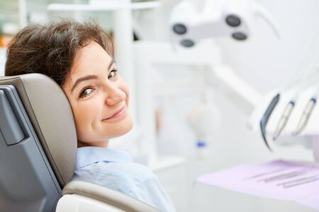 Young patient in the dentist chair is waiting for the preventive treatment in the dental office