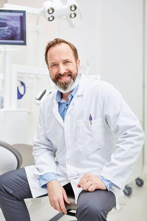 Dentista amable y exitoso en bata blanca está sentado en su consultorio dental