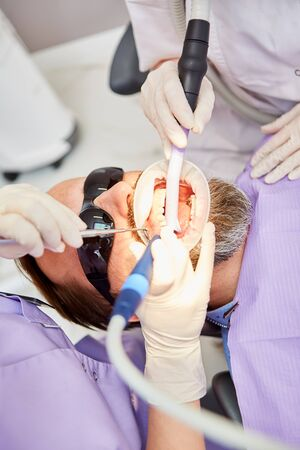 Dentist with drill removes tartar or tooth decay during a treatment at the dental office