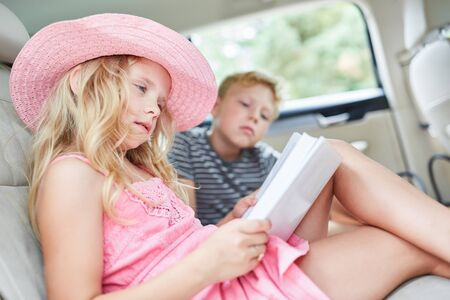 Girl in the backseat in the car is reading a thrilling book on the trip Imagens