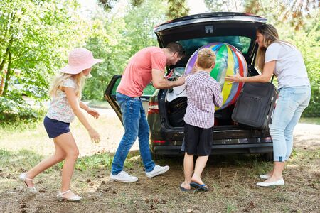 Family and children together load the car with luggage before the summer vacation Reklamní fotografie - 132228045