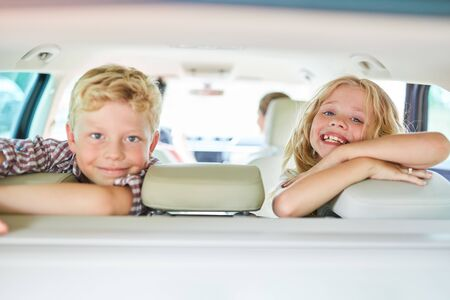 Two children in the back seat in the car are looking forward to the summer holidays