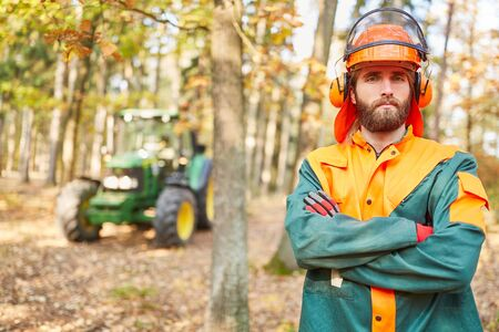 Self-confident forest worker or forestry worker in protective clothing during forest work Stock Photo