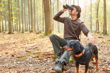 Forester with hare as a hunting dog observes nature with the binoculars 免版税图像