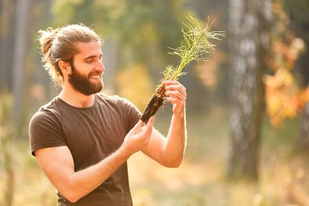 Young forest worker or farmer with a pine seedling during afforestation Stockfoto
