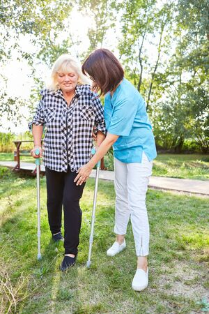 Nursing woman helps senior woman with crutches while walking learning in rehab