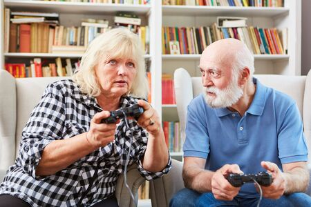 Senior couple as vital retiree at video game console in the living room
