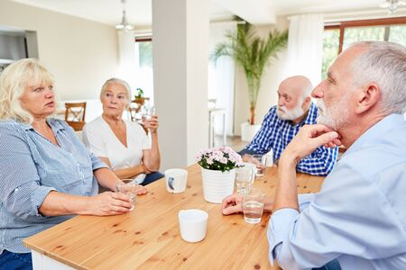 Seniors in the common room in the nursing home during a relaxed conversation