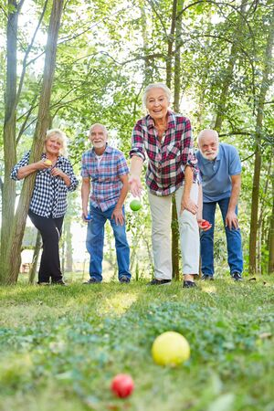 Group of seniors playing bocce or boules play together in nature