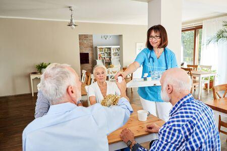 Nursing lady distributes medicine to seniors in a nursing home or nursing home