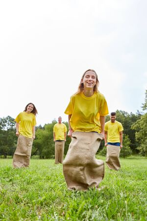 Young woman and her crew have fun with sack jumping on a sports festival