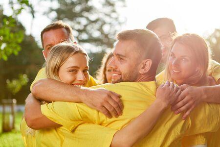 Succesvol jong team omhelst elkaar vrolijk tijdens de teambuilding workshop Stockfoto