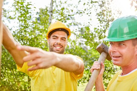 Two construction workers are working in teamwork on a construction site while building a house