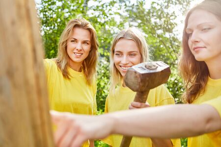 Group of women work in teamwork with a sledgehammer in a workshop