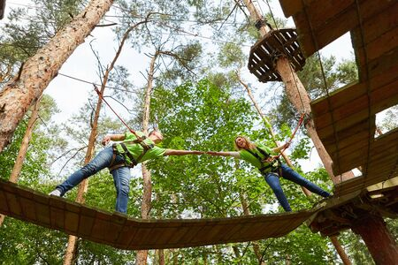 Two climbers help themselves in the high wire garden on a bridge as a team building activity 版權商用圖片
