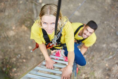 Young woman in climbing park roped on the ladder during teambuilding workshop