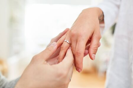 Male hand puts a wedding ring or engagement ring on ring finger
