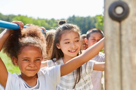 Girl and multicultural friends do gymnastics on climbing frame on playground