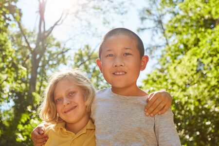 Asian boy and his european friend in summer camp in summer Stock Photo