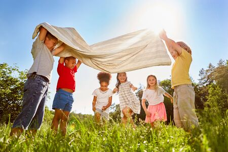 Group of kids plays together with a towel on a meadow in summer