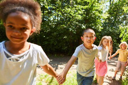 Group of children in the international kindergarten go hand in hand