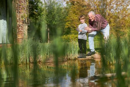 Grandpa and grandson have fun fishing together by the lake in summer