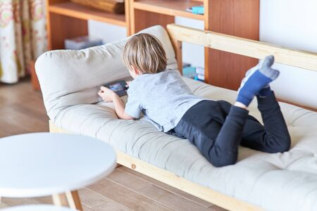 Boy is lying on the couch and playing a video game on the smartphone