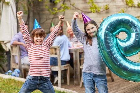 Siblings celebrate together child birthday with family in the garden in summer