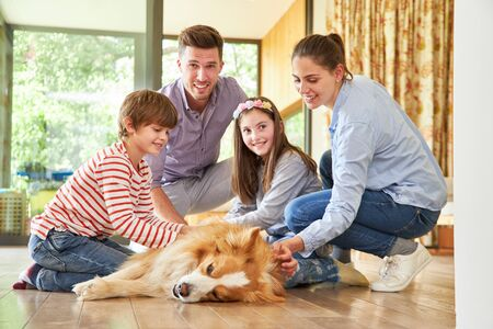 Genitori e bambini felici accarezzano il loro cagnolino in soggiorno