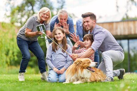 Family with children and grandparents have fun making selfie in the garden Imagens